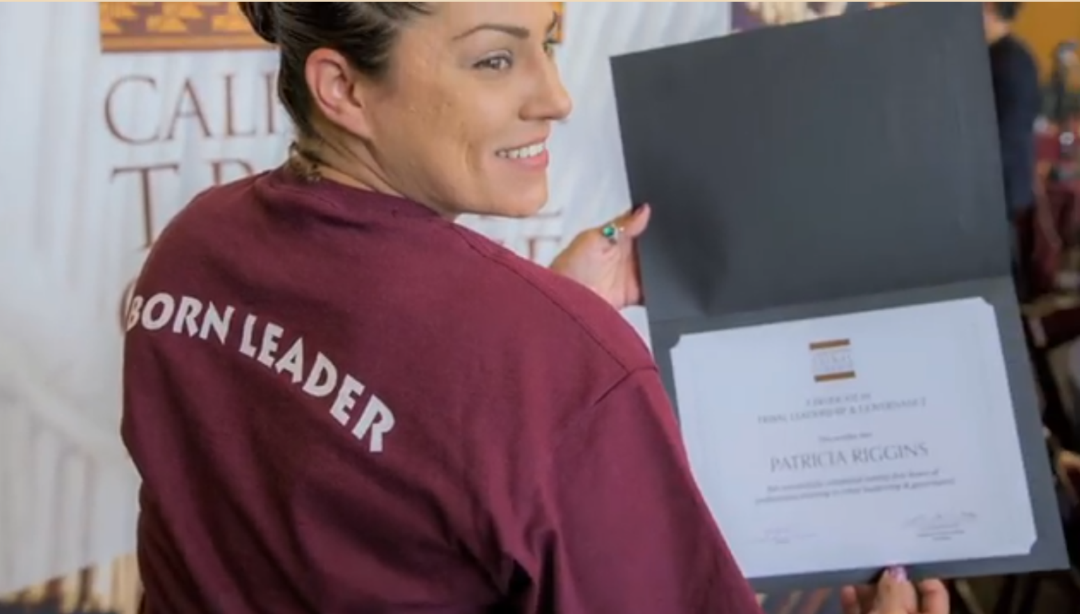California Tribal College Student holding diploma and smiling. On the back of her t-shirt are the words Born Leader